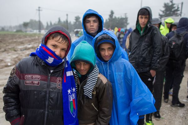 Refugees who have just arrived by bus queue in the rain at a refugee transit camp on the border between Greece and