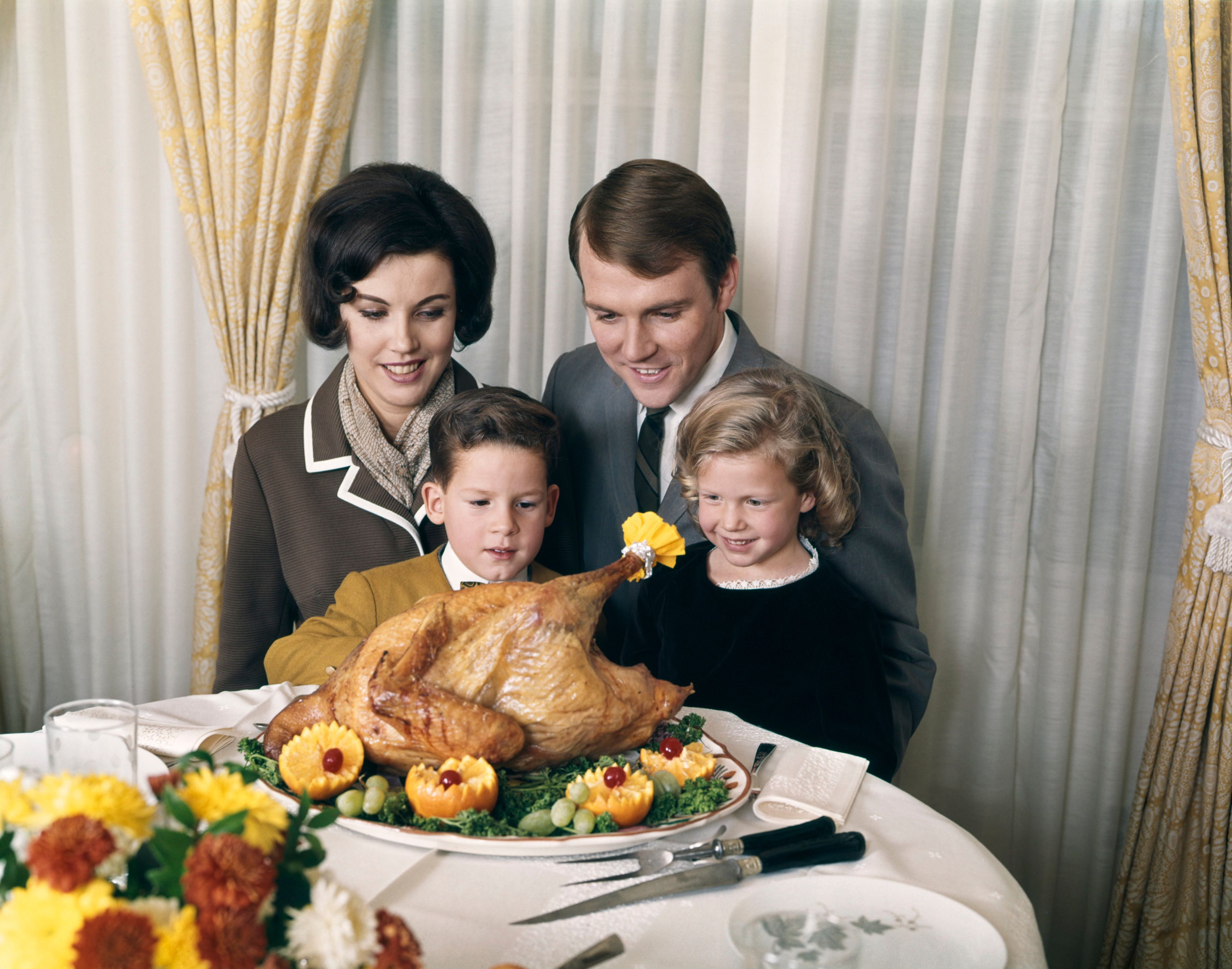 1960s 1970s FAMILY PORTRAIT WITH HOLIDAY ROASTED TURKEY ON DINING TABLE  (Photo by H. Armstrong Roberts/ClassicStock/Getty Images)