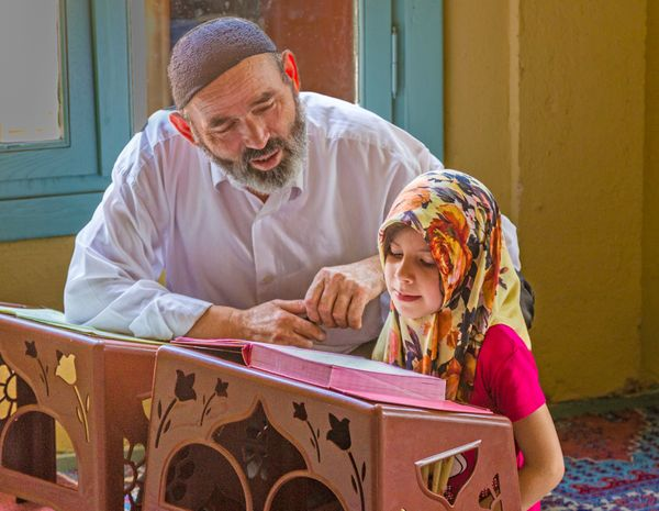 "*Highly Commended*<br>An imam teaches a young girl to read Islam's holy book. The judges praised the photo's ""superb composit"