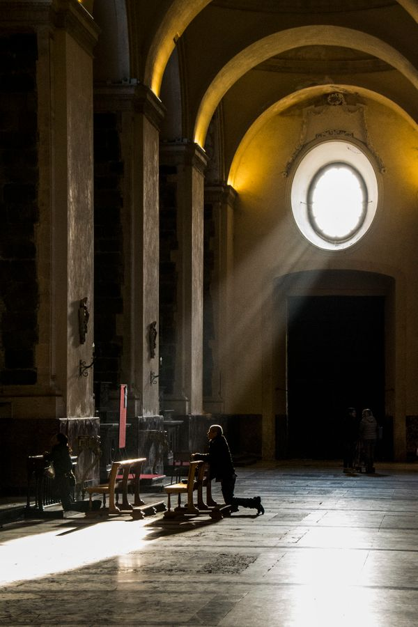 A worshipper prays at a side altar in the Duomo di Siracusa (Cathedral of Syracuse) in Ortygia, Sicily. The judges said