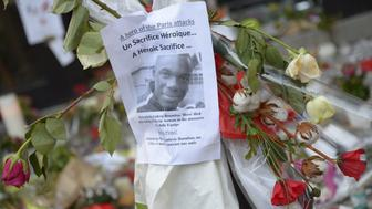 Flowers have been laid next to a placard bearing the picture of Ludovic Boumbas, one of the victims, at a memorial at the site of the attack at the Cafe Belle Equipe on rue de Charonne in the 11th district, on November 18, 2015 in Paris. Gunmen and suicide bombers went on a killing spree in Paris on Friday night, attacking a concert hall, bars, restaurants and the Stade de France. Islamic State jihadists operating out of Iraq and Syria released a statement claiming responsibility for the coordinated attacks that killed 129 people and left 352 others injured.  AFP PHOTO / BERTRAND GUAY        (Photo credit should read BERTRAND GUAY/AFP/Getty Images)