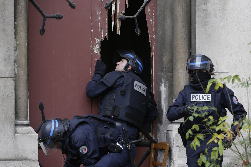 Police break a door to enter a church in Saint-Denis to secure the area after special forces raided an apartment.
