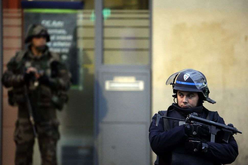 A police officer stands guard next to a French soldier.
