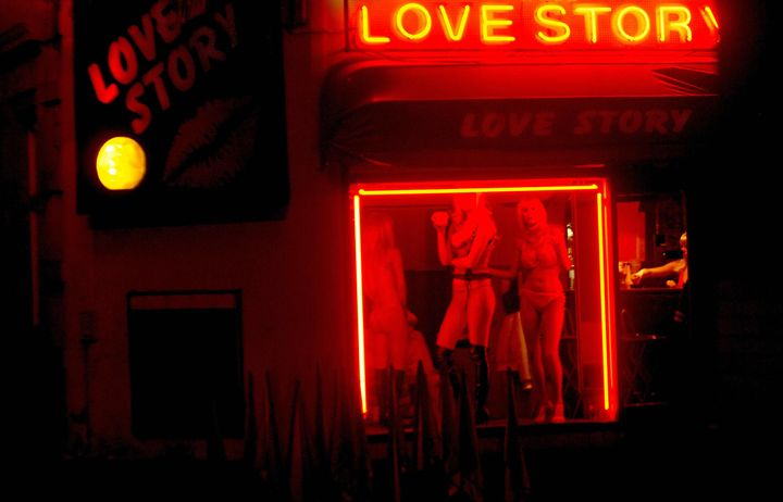 Cheb, CZECH REPUBLIC: Prostitutes wait for clients behind a window of a brothel 14 December 2006 on a highway near the city o
