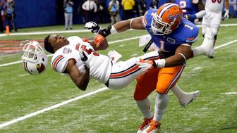 Florida linebacker Jon Bostic (1) hits Louisville quarterback Teddy Bridgewater (5) hard enough to dislodge his helmet in the first quarter of the Sugar Bowl NCAA college football game Wednesday, Jan. 2, 2013, in New Orleans. (AP Photo/Bill Haber)