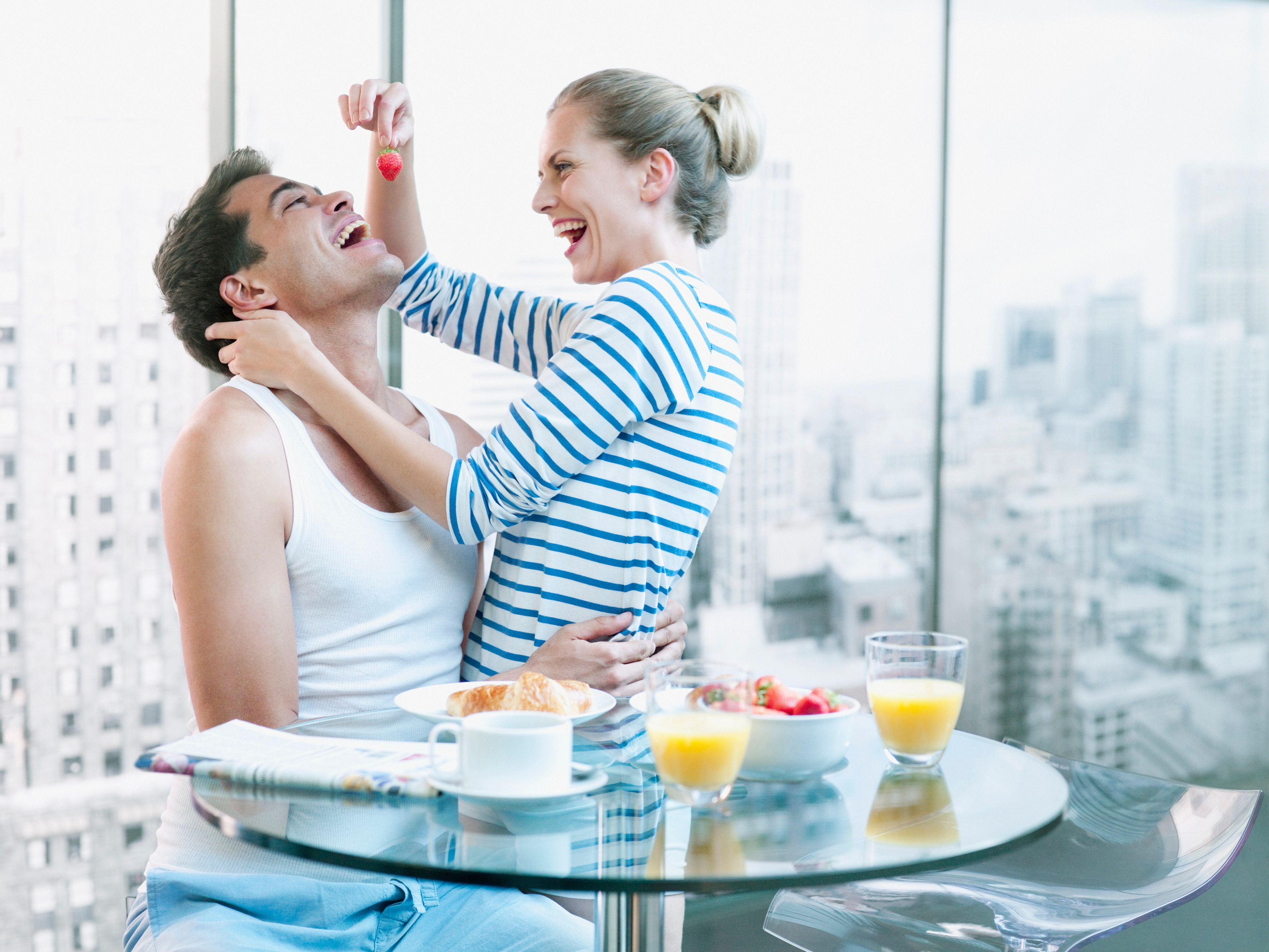 Playful woman feeding strawberry to husband at breakfast