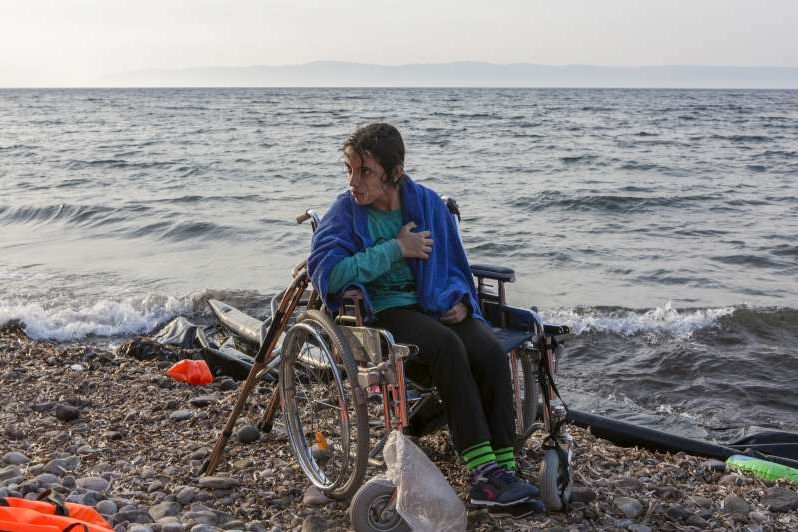 Syrian refugee Nujeen, 16, waits to be carried from the shoreline to the road after landing on the Greek island of Lesbos wit