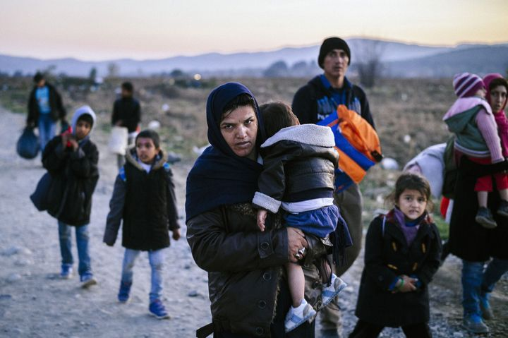 A woman carries a child as migrants and refugees walk near Gevgelija, Macedonia, after crossing the Greece-Macedonia border o