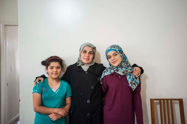 Hajar, Amira and Nabiha Darbi pose in their new living room in New Jersey. The Darbi family is one of many Syrian refugee fam