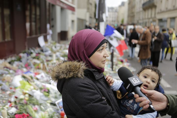 A Muslim woman is interviewed as she is paying her respects at the memorial outside Le Carillon for the people killed here du
