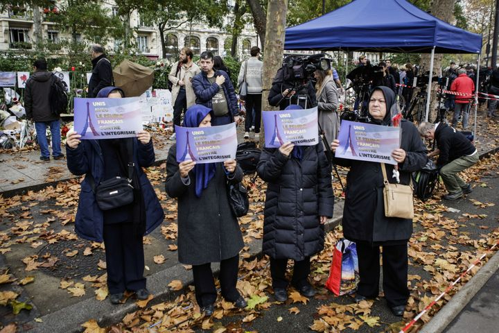 Muslim women hold placards against fundamentalism during the commemoration for victims of Paris terror attacks in front of Ba