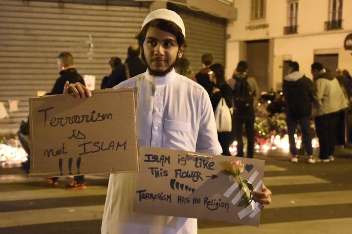 A Muslim holds placard reading 'Terrorism is not Islam. Islam is like this flower. Terrorism has no religion' during a gather