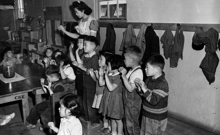 Aiko Sumoge, an assistant teacher, leads a kindergarten class singing an English folk song at the internment relocation