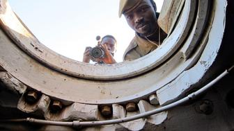 Yassin Hassen, a reporter for Nuba Reports, a website started by American Ryan Boyette, films inside a tank captured by rebels in Sudan's Nuba Mountains. (Alan Boswell/MCT via Getty Images)