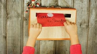 A Child placing letter to Santa in the mailbox. The box is hanging on an old wooden wall.You can see only the child's arms.