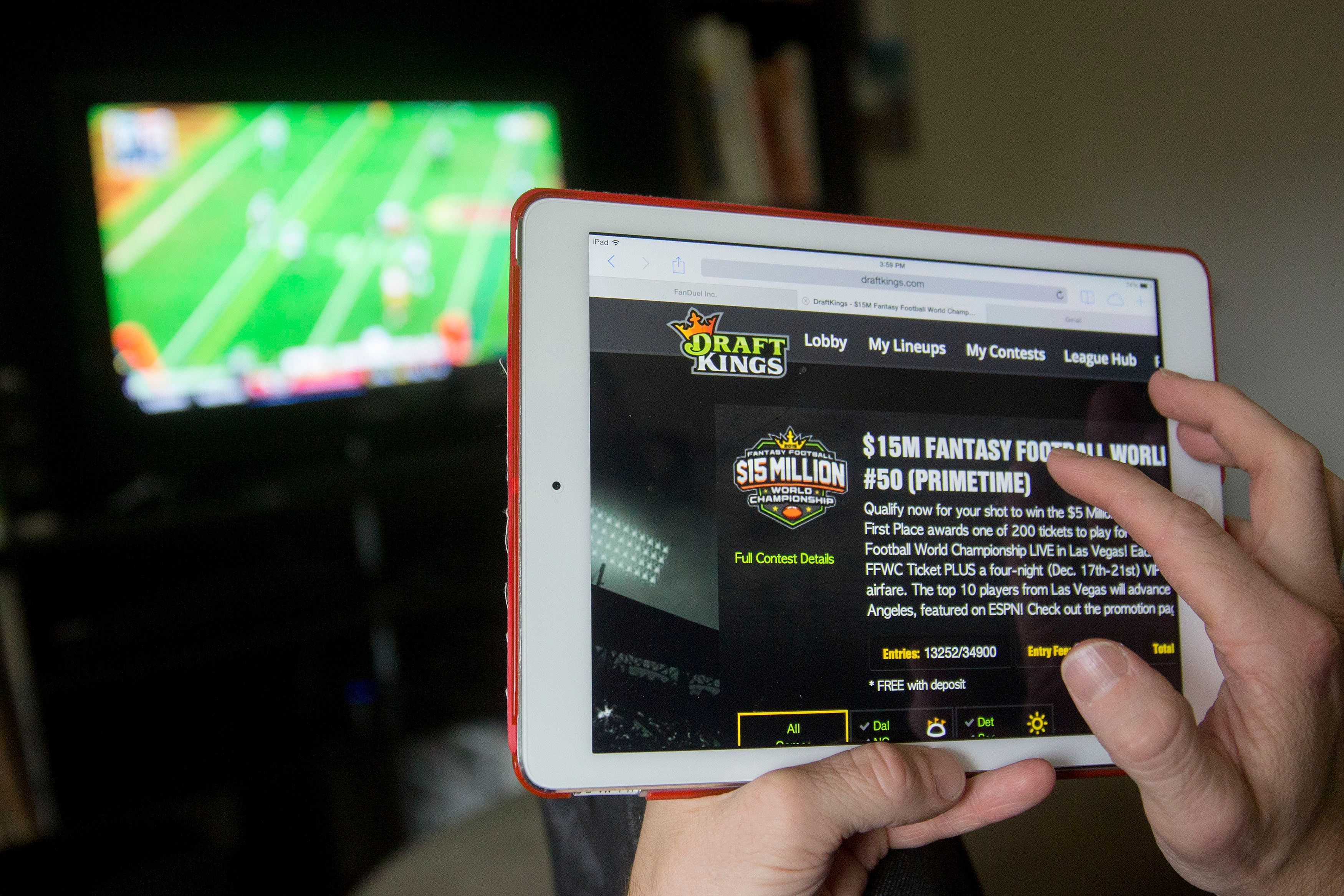 The DraftKings Inc. website is arranged for a photograph on an Apple Inc. iPad in Washington, D.C., U.S., on Sunday, Oct. 4, 2015. Fantasy sports companies DraftKings Inc. and FanDuel Inc. raised a total of $575 million in July from investors including KKR & Co., 21st Century Fox Inc. and Major League Baseball to attract players to games that pay out millions of dollars in cash prizes in daily contests. Photographer: Zia Morales/Bloomberg via Getty Images