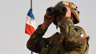 A French soldier of the 93rd Mountain Artillery Regiment, part of the French Army's 'Operation Barkhane', an anti-terrorist operation in the Sahel, looks through binoculars while patrolling on an armoured vehicle a track between M'Bouna and Goundam in the Timbuktu region on June 5, 2015, during the joint operation 'La Madine 3'.  AFP PHOTO / PHILIPPE DESMAZES        (Photo credit should read PHILIPPE DESMAZES/AFP/Getty Images)