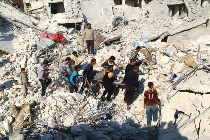 People with a rescue team inspect a collapsed building and try to rescue people after an Assad-ordered airstrike over residen