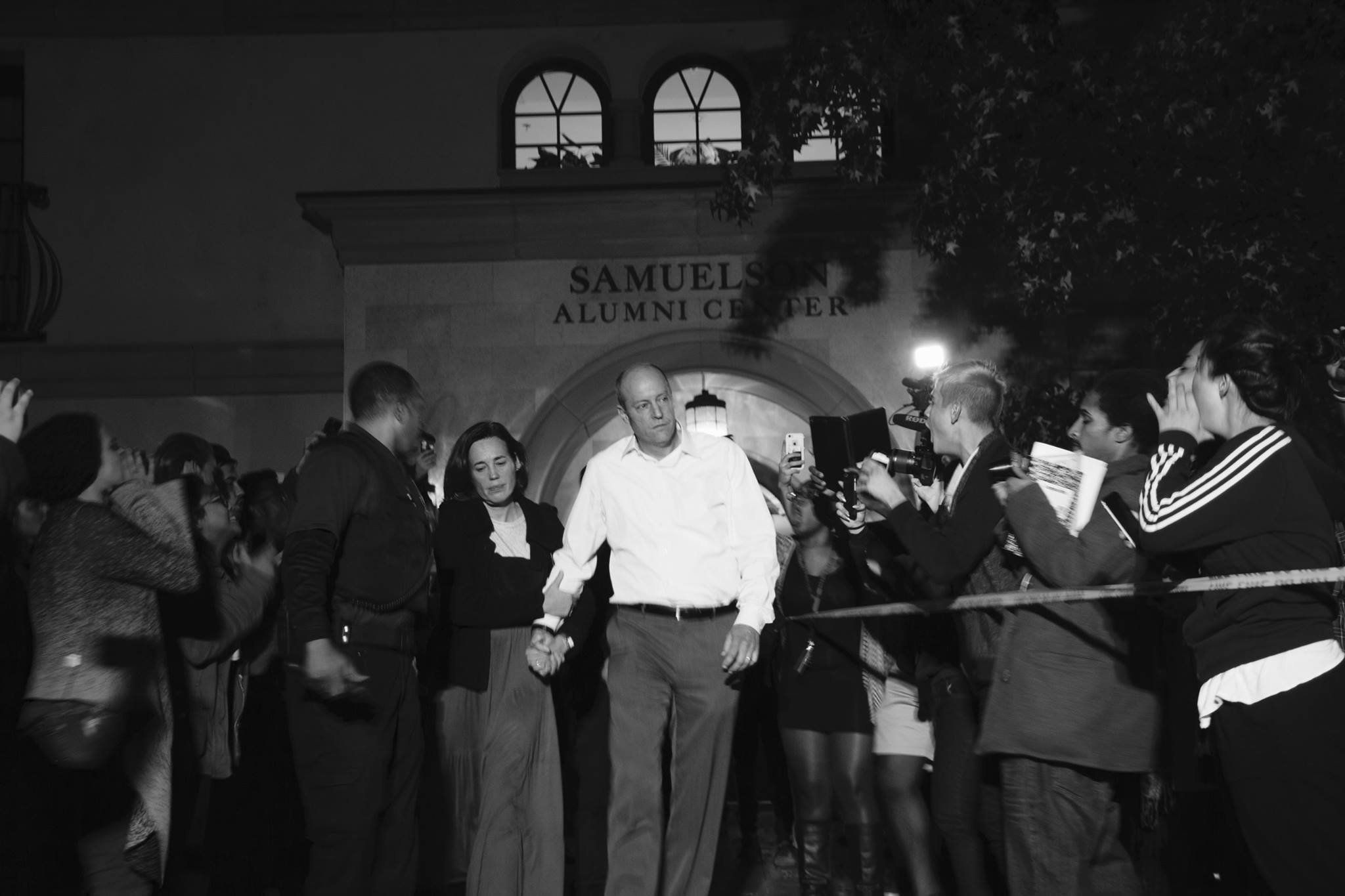 Occidental College President Jonathan Veitch is escorted out of a building where protesters had swarmed outside, calling for