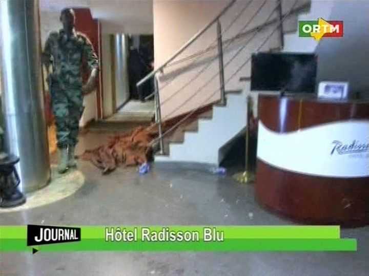 In this TV image taken from Mali TV ORTM, a member of the security forces walks past a body lying covered on the floor in the