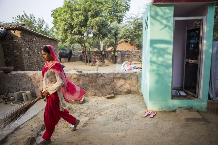 A resident walks away after cleaning a toilet block, recently built by villagers with support from Sulabh International Socia