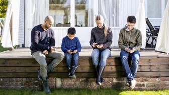 Family of four using mobile phones at yard