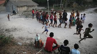 MARANHAO STATE, BRAZIL - NOVEMBER 20:  Residents gather and dance during the traditional Bumba Meu Boi ceremony marking Brazil's National Day of Black Consciousness in the Imbiral quilombo, which community members say is being heavily encroached upon by illegal logging and cattle ranching, in the Amazon basin on November 20, 2014 in the Pedro do Rosario municipality of Brazil. Quilombos are communities usually made up primarily of descendants of escaped slaves who fled to rural areas in Brazil and formed autonomous communities. Residents of the Imbiral quilombo, which is officially recognized, say illegal logging and ranching has rapidly depleted their ancestral territory and some community members have received death threats for resisting deforestation. The non-governmental group Imazon recently warned that deforestation in Brazil's Amazon basin skyrocketed 450 percent in October of this year compared with the same month last year. The United Nations climate conference is scheduled to begin December 1 in neighboring Peru.  (Photo by Mario Tama/Getty Images)
