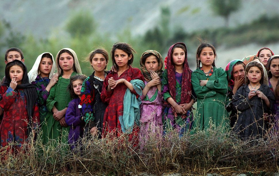 Girls from the remote village of Ghumaipayan Mahnow in northern Afghanistan, near the border with Tajikistan, watch as U.N. w