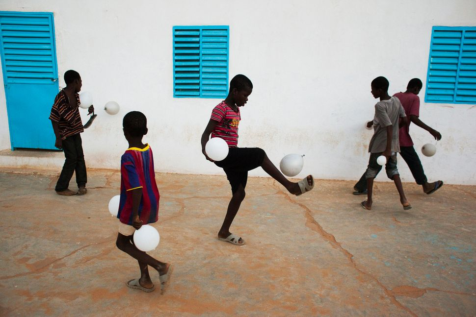 A group of boys play soccer with balloons after attending a dance recital about water scarcity in the city of Kaedi in the Go
