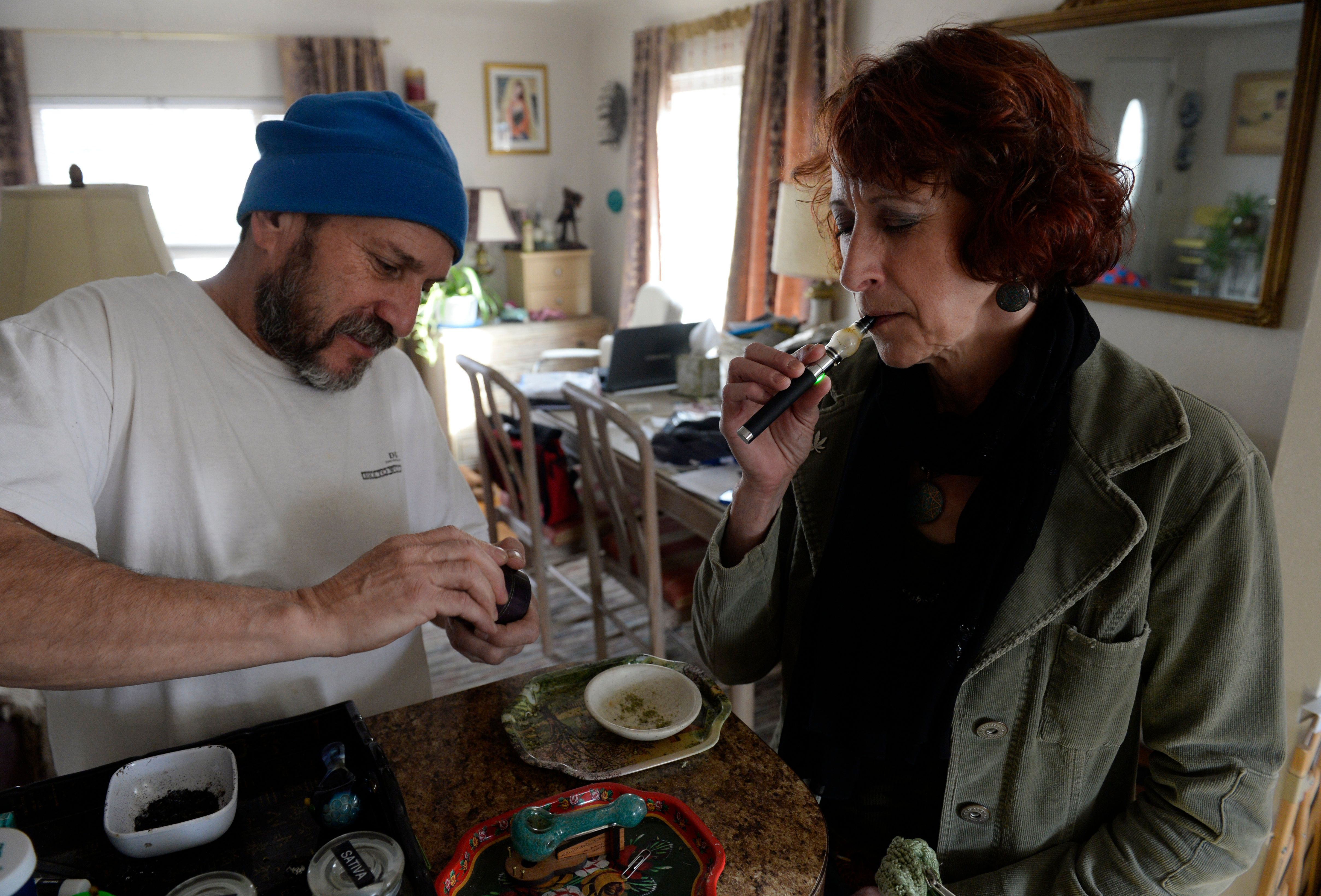 DENVER, CO - DECEMBER 16: Medical marijuana patient, Teri Robnett, right, uses a vape pen, vaporizing cannabinoids to manage cronic fibromyalgia December 16, 2014. Her husband, Greg Duran, uses a grinder to grind marijuana to use in a larger vaporizer machine for Teri, who medicates throughout the day. (Photo by Andy Cross/The Denver Post via Getty Images)