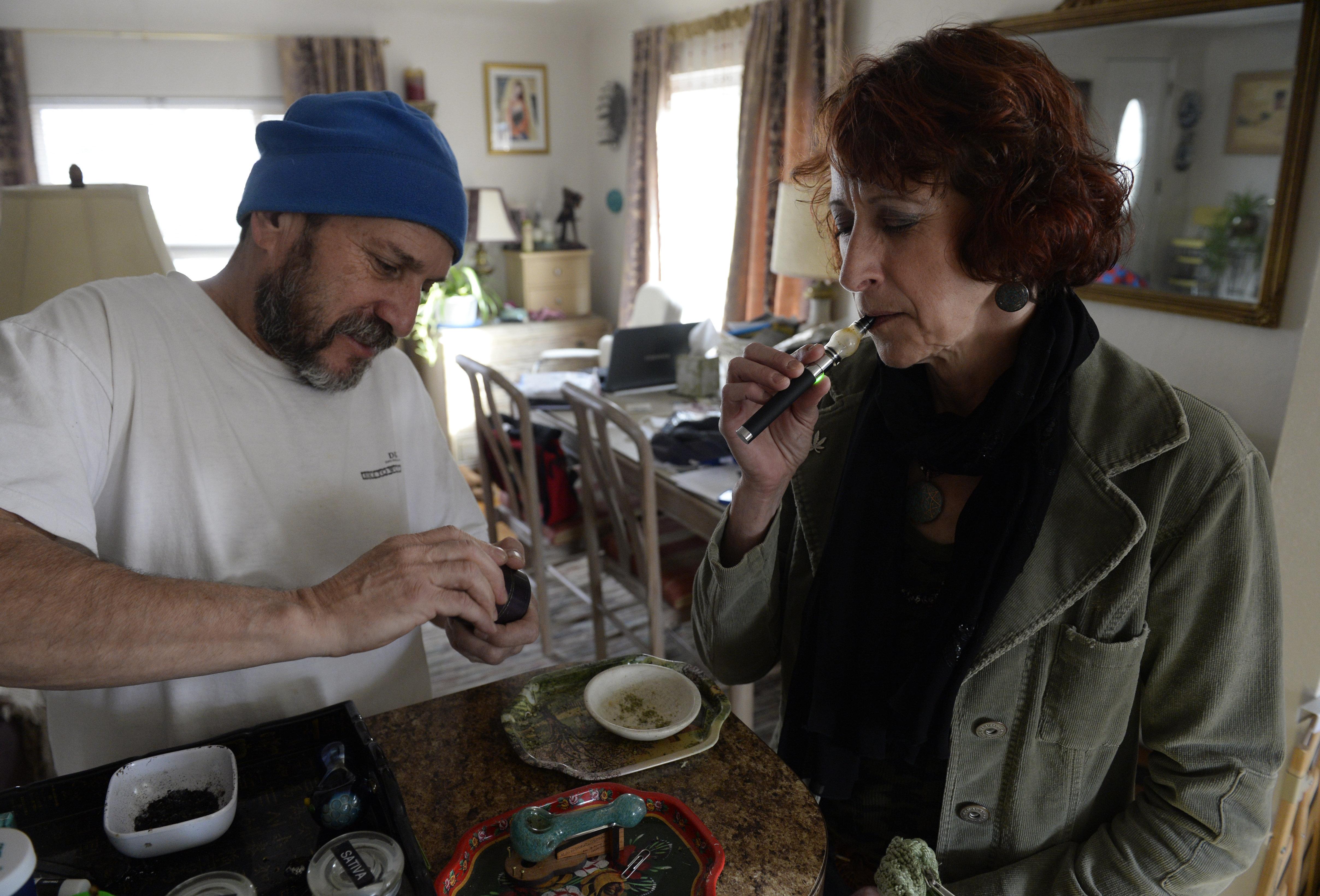 Colorado medical marijuana patient Teri Robnett, right, uses a vape pen to manage chronic fibromyalgia. A majority of Colorad