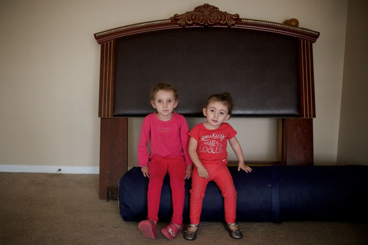 Syrian refugees Hiam Alawad, left, 4, and Dana Alawad, 2, sit by a bed backboard in their new home in Bloomfield Hills, Michi
