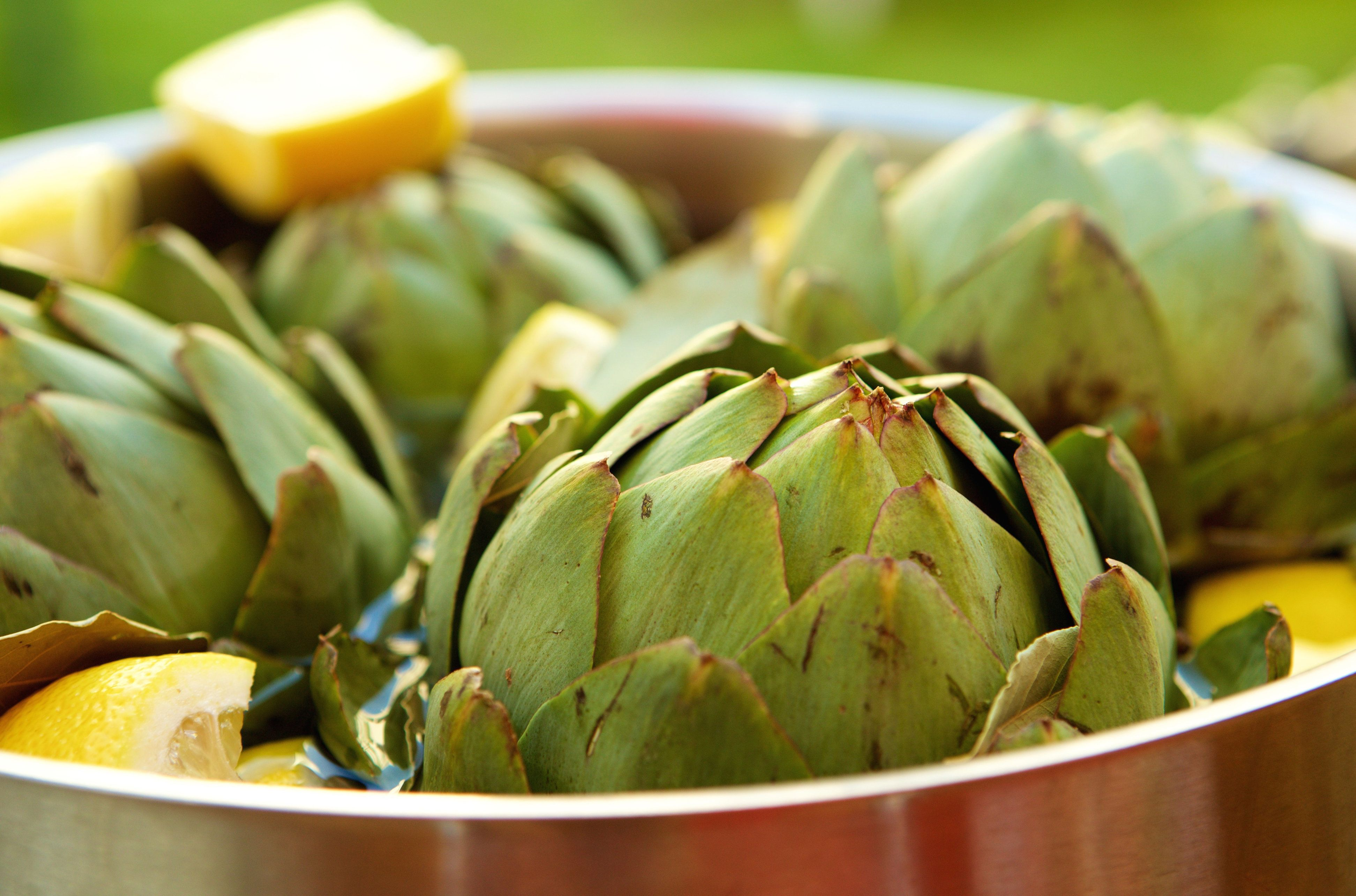 First, prepare your artichokes by trimming the stems and spiky points from the leaves. Then, pour a cup of water into your ri