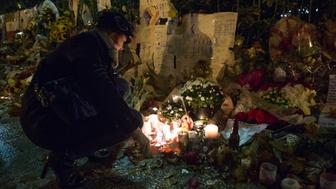 REPUBLIQUE DISTRICT, PARIS, FRANCE - 2015/11/20: A woman light candles at a makeshift memorial in front of 'Le Bataclan' concert hall in the 11th district of Paris.  Islamic State (ISIS) jihadists claimed coordinated attacks in central Paris that killed at least 129 people and wounded hundreds at a concert hall (Le Bataclan), restaurants and the national stadium (Stade de France). (Photo by Guillaume Payen/LightRocket via Getty Images)