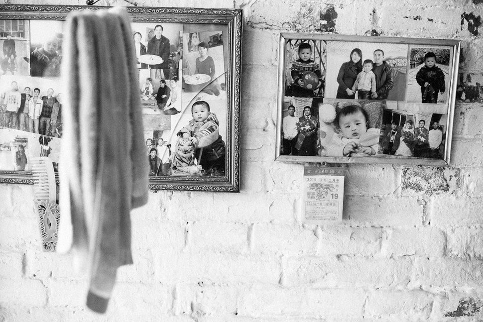 Photos of Liu's family hang in their home.