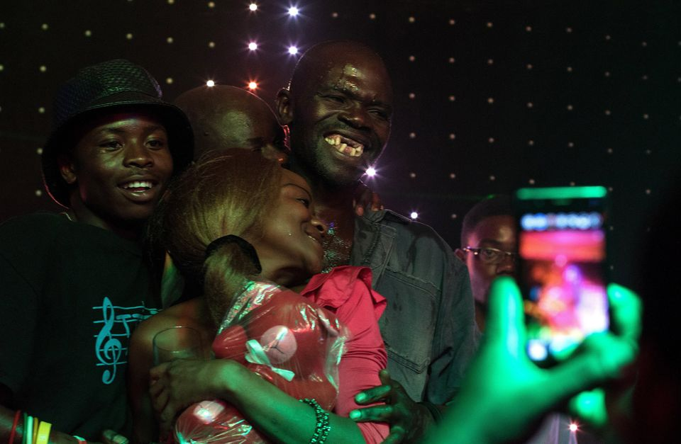 Newly crowned 'Mr Ugly' Zimbabwe, Maison Sere, celebrates his victory with members of the audience during the 'Ugliest Man' c