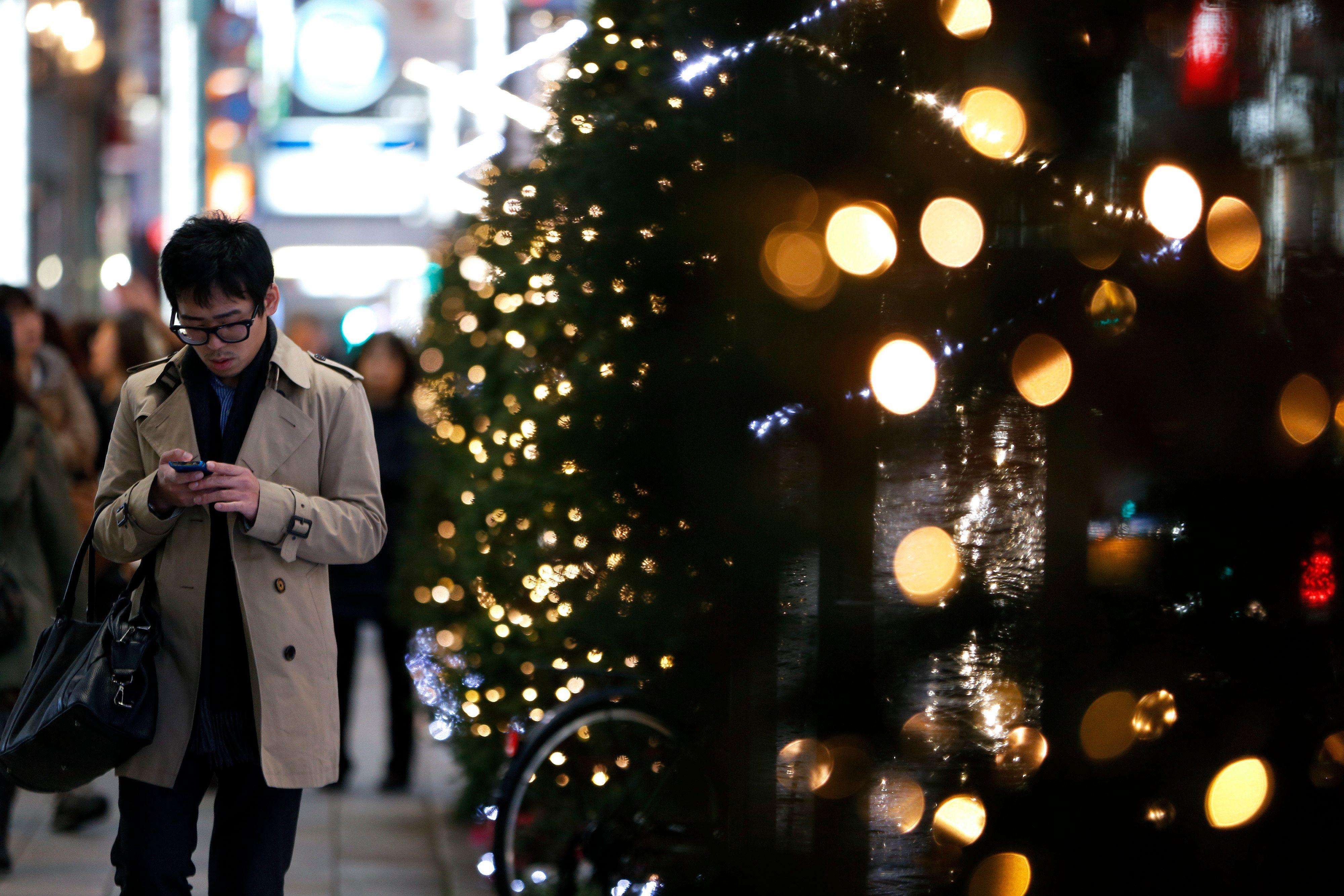 A pedestrian uses a mobile phone as he walks along a street while Christmas trees stand on display in Tokyo, Japan, on Thursday, Dec. 5, 2013. The cabinet approved an 18.6 trillion yen ($182 billion) economic package to cushion the economic blow from a sales-tax increase next April. The package includes 5.5 trillion yen in spending and the government projects it will boost real gross domestic product by about 1 percent and create about 250,000 jobs. Photographer: Kiyoshi Ota/Bloomberg via Getty Images