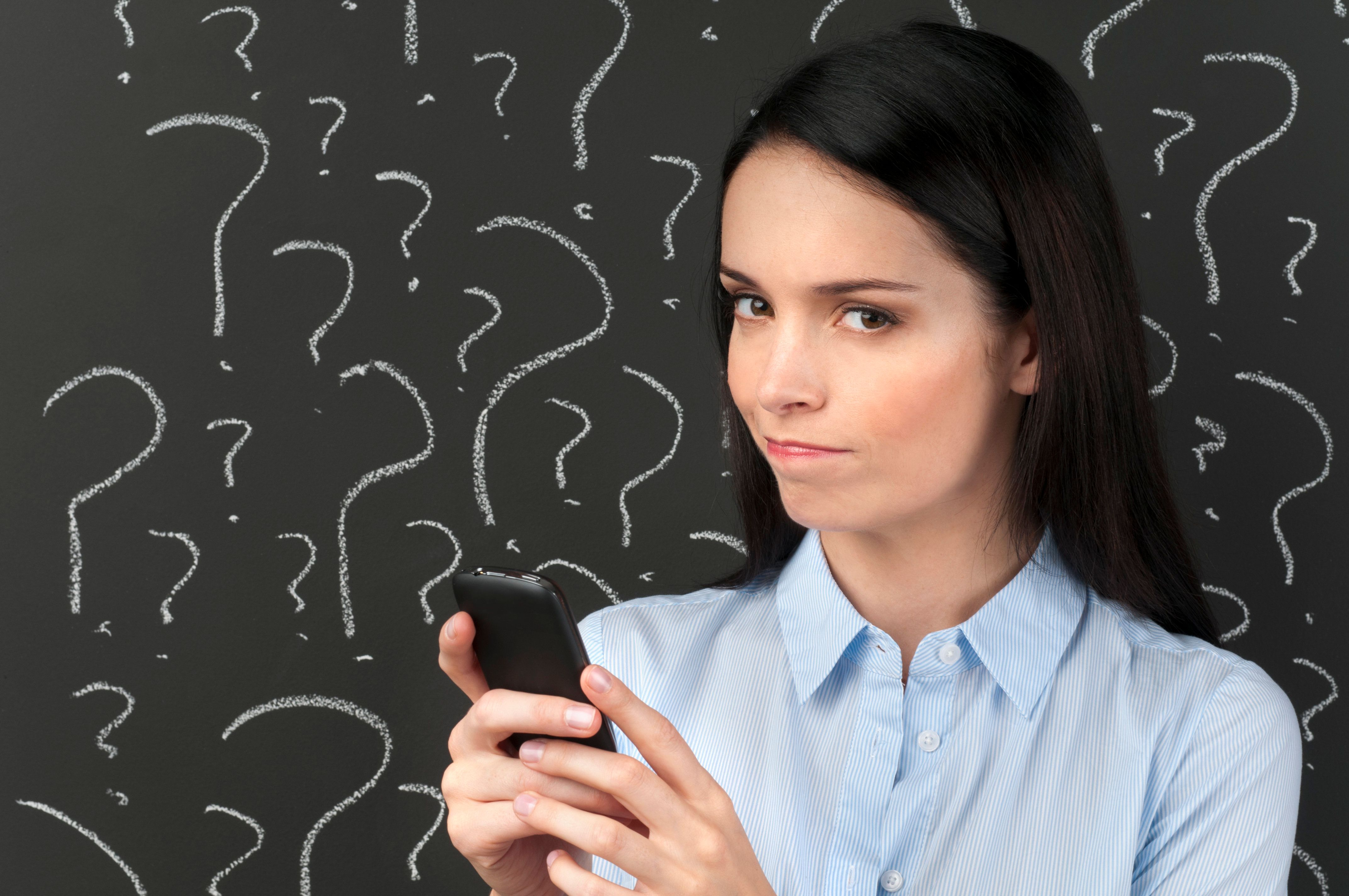 Mobile phone service concept - Woman texting with question marks on a blackboard.