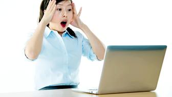 Surprised businesswoman looking at laptop with her mouth open.