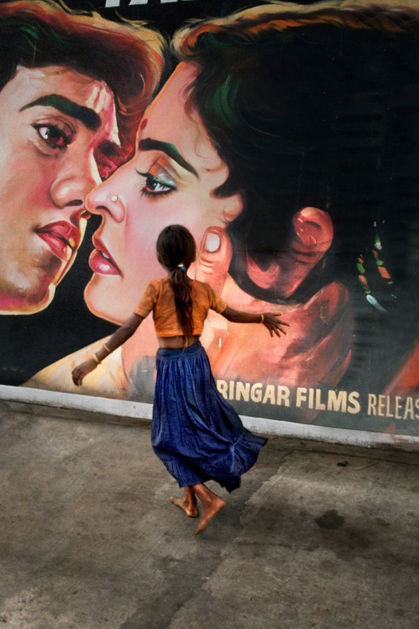 Young girl runs past movie poster, Mumbai, Maharashtra; 1993
