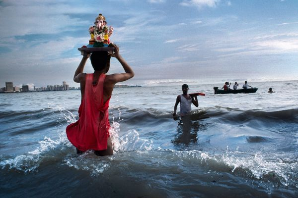 Hindu devotee carries statue of Lord Ganesh into the waters of the Arabian Sea during the immersion ritual off Chowpatty Beac