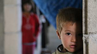 HATAY, TURKEY - NOVEMBER 21: A Syrian refugee kid fled from his home due to civil war is seen at a house in Reyhanli district of Hatay on November 21, 2015. Syrian refugee families who fled their country due to the ongoing civil war try to hold on to life as they live in rented houses, tents and storehouses. (Photo by Cem Genco/Anadolu Agency/Getty Images)
