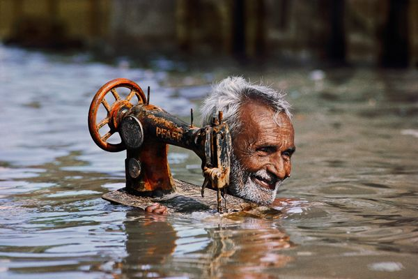 Tailor carries his sewing machine through monsoon waters, Porbandar, Gujarat; 1983