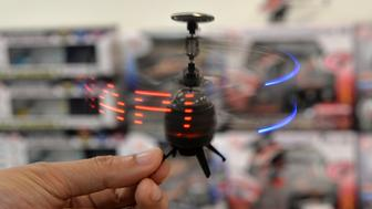 Japan's toy maker Kyosho employee displays the company's palm sized infrared controled drone 'Neon Messenger', which can displays LED messages while flying at a toy trade show in Tokyo on September 11, 2013. Kyosho will put it on the market end of this month for the Christmas gift. AFP PHOTO / Yoshikazu TSUNO        (Photo credit should read YOSHIKAZU TSUNO/AFP/Getty Images)