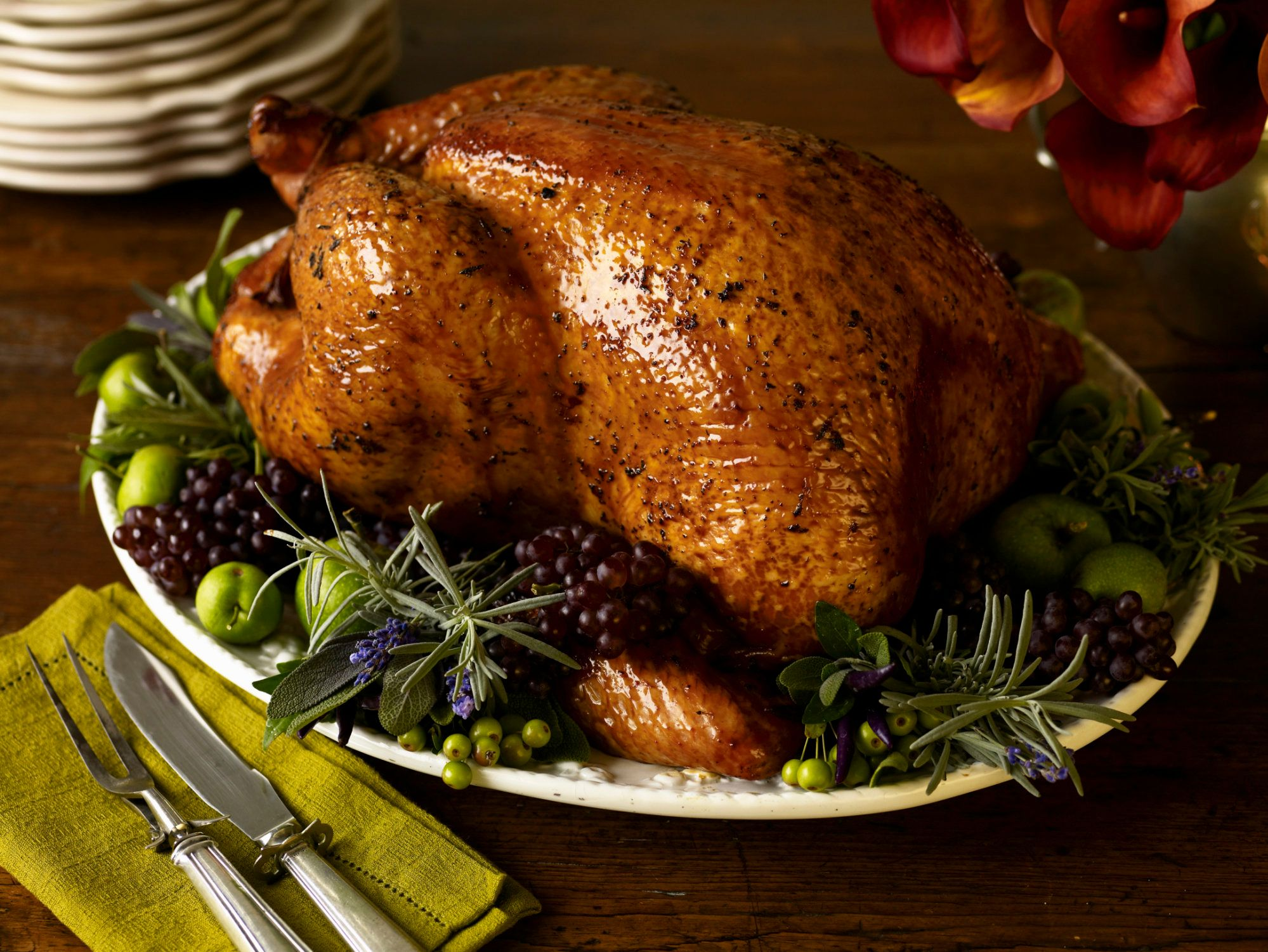 Roast turkey with garnish and platter on rustic wooden table