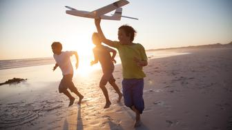 Boys, aged 9-10,  running along a beach at sunset with a toy plane