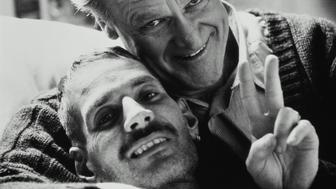 Father embracing son with AIDS in bed (B&W)