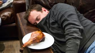 A Caucasian man takes a nap in a comfortable leather chair after eating too much for Thanksgiving dinner.  A turkey leg sits on a plate on the armrest.  Shot with Canon 5D Mark 3.  rm
