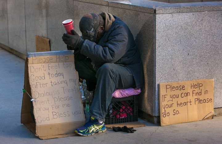 CHICAGO, IL - OCTOBER 10: A homeless man begs for money in front of the Wrigley Building on October 10, 2015 in Chicago, Illi