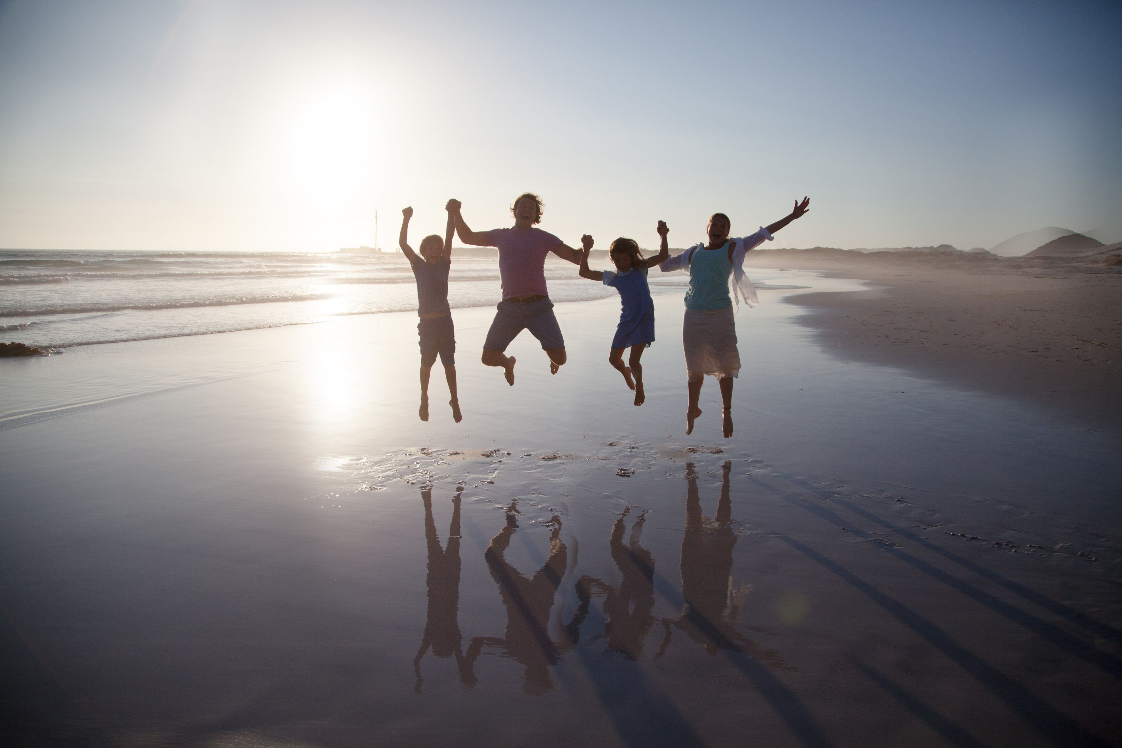 Family with two children  jumping together on a beach at sunset
